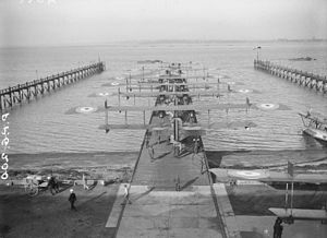 Seaplane Experimental Station -  Felixstowe F.2Bs starting out on patrol. Some of the motor boats that towed them can be seen. A converted seaplane lighter with a flight deck moored on the right.