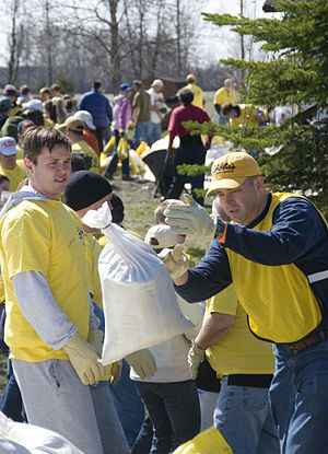 Mormon Helping Hands - Volunteers wearing yellow Mormon Helping Hands shirts and vests help clear thousands of used sand bags from a Moorhead, Minnesota property on April 25, 2009. Mike Moore/Federal Emergency Management Agency.