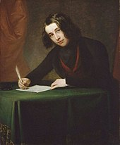 A man with shoulder-length black hair, sitting at a desk, writing with a quill