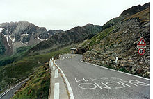 A curving, ascending road, up against a rocky hillside. There is writing in Italian on the road, a sign on the roadside, and further mountaintops visible in the background.