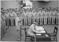 General Douglas MacArthur signs as Supreme Allied Commander during formal surrender ceremonies on the USS MISSOURI in... - NARA - 520694.tif