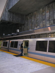 A near-empty station platform of a train station, with a person about to enter a train