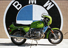 Green BMW R90S Motorcycle Parked In Front Of A Brick Wall Which Is Painted  With A
