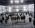 Group of Young Women Students in School Uniform at Gym Class; Some with Indian Clubs; Some on Parallel Bars, Others on Catwalk Above Gym Floor 1880.jpg