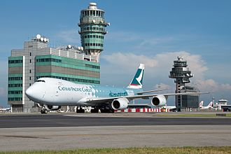 Hong Kong International Airport - The airport control tower and a taxiing Cathay Pacific Cargo Boeing 747-8F