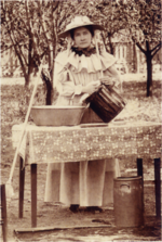 Sepia-toned photograph of a woman in a bonnet by a table outdoors.