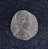 A small silver coin mostly consisting of a human head and shoulders. The shape is irregular and there is only a vestige of writing.
