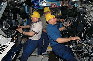 Expedition 15 - Cosmonauts Fyodor Yurchikhin (left) and Oleg Kotov, along with astronaut Clay Anderson (right) wearing yellow hard hats in a less serious moment.