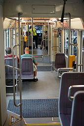 Interior of a streetcar, with several seats facing forwards and backwards, a two-step stairway, a yellow fare validation machine, and several poles.