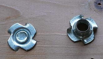 T-nut - T-nuts. The left one has been inserted in the wood and a bolt has been screwed in from the other side.