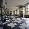 Interieur, overzicht van de hoofdentree met een arcade op zuilen, tegelvloer en klassieke beelden - 's-Gravenhage - 20387426 - RCE.jpg