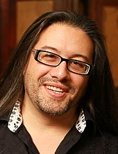 Face of a smiling man with long black hair and glasses