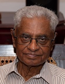 An image of a grey-haired Indian man with glasses