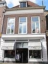 foto van Huis met gepleisterde beganegrond met jongere winkelpui in lijstgevel met laat-gotische sporen en met gemetselde schoren die de Houtzagersteeg tussen de nrs. 162 en 164 overspannen