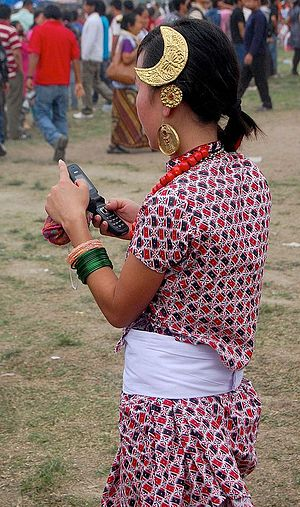 Sakela - Kirati lady using cellphone wearing traditional costume at Sakela, Tudhikhel Nepal 2009