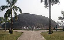 Uma colina muito grande atrás de duas palmeiras e uma avenida, onde acredita-se que o Buda tenha sido cremado
