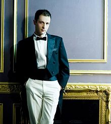 A dark haired man in a tailcoat and a kummerbund, dark bow tie, both hands in the pockets of light-coloured trousers.