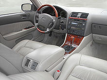 Automobile front interior, showing center armrest, front seat cushions, console, and dashboard.