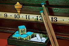 Vue rapprochée d'une bande de notation horizontale montrant les chiffres 9, 10, 11, 12 et 13, avec un pointeur en céramique reposant au-dessus du 10, deux pointes de repère reposant contre le 12 et une boîte de craie posée sur une étagère en dessous
