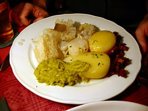 Traditional Norwegian lutefisk with potato, bacon, mashed peas.
