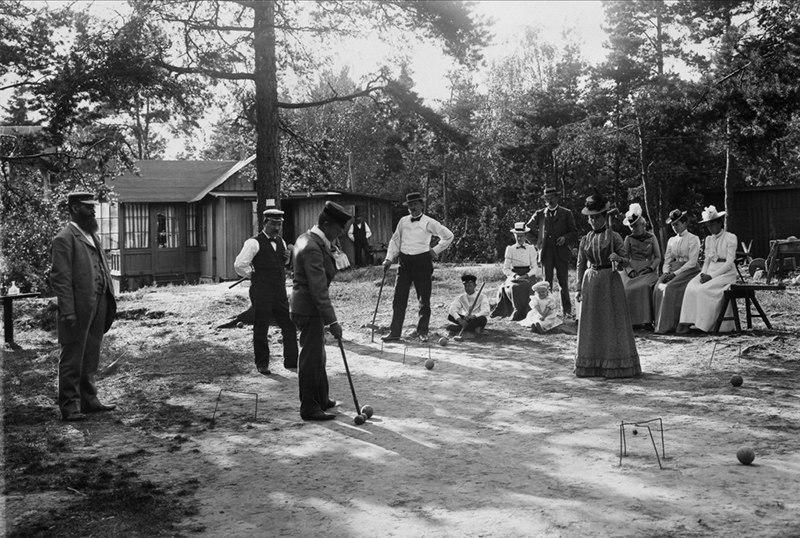 Män och kvinnor spelar krocket framför hus på Lidingö - Nordiska Museet - NMA.0040765