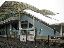 An at-grade train station situates behind two train tracks