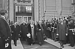 Zwart-witfoto van individuen die uit een gebouw komen;  in het midden een glimlachende vrouw, met een hoed op, een lange kraag en een bontjas, houdt de arm van een man in een driedelig pak, grijswit haar, grijzende snor, hoed in de hand;  ze worden omringd door andere mannen in burgerkleding en Republikeinse Garde