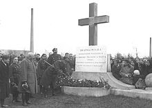 A large group of people, many of them in Polish Army winter uniforms, surround a monument. The monument consists of a concrete base and a 5-metre-high cross, with a large stone tablet in front of it. The text on the tablet reads (in Polish): Brotherly grave of heroes fallen in defence of the fatherland in 1920; the monument was funded by workers of the Polish Bank in Warsaw. In the background a tall factory chimney.