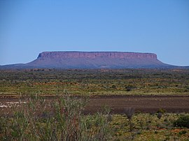 Photo of a wide, flat-topped plateau across the horizon, rising from surrounding scrubland