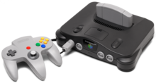 On the left, a three-pronged, handheld controller with a central analog stick and multiple buttons. On the right, a black electronics unit that accepts a light gray cartridge on the top and controllers (via ports) on its front.