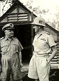 Two men in light-coloured military uniforms, one wearing a pith helmet