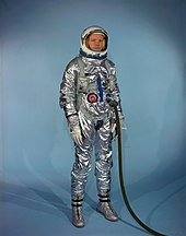 Armstrong standing up, wearing an early space suit. It is highly reflective silver in appearance. He is wearing the helmet, which is white, with the visor raised. A thick dark hose is connected to one of the two ports on the front abdomen of the suit.