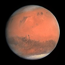 Mars appears as a red-orange globe with darker blotches and white icecaps visible on both of its poles.