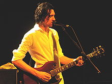 A thirty-year-old man is playing a six-string electric guitar while singing into a microphone.