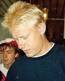 Peter Schmeichel, with blonde hair and wearing a dark blue sweater, looks down towards his left with an unidentified man in the left background.