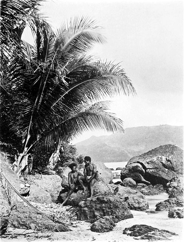 Black and white photograph of two men sitting on a rock on a beach.