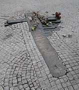 Une croix stylisée au sol, entourée par les pavés du sol, avec des roses.