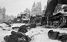 A road in the middle of forest and snow, a frozen body in front and destroyed vehicles in behind.