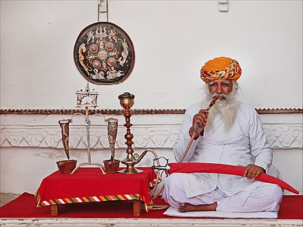 An Indian man smoking Tobacco on hookah, Rajasthan, India. Rajput (Jodhpur) (8411728143).jpg