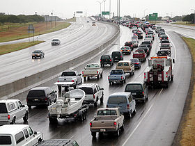 Traffic along a wet highway. Most of the cars are on the right side of the road; however, at least two cars are on the left side.