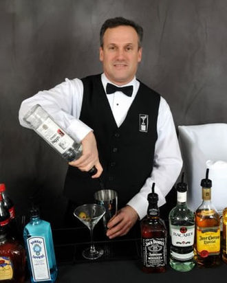 Bartender - A bartender pouring some vodka in to the metal cup of a cocktail shaker