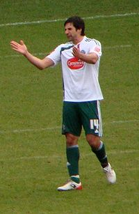 A man wearing a white and green football kit.