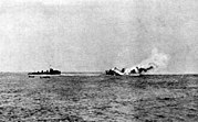 A large, burning warship rolling over and sinking; a smaller, black ship is nearby with two small boats.