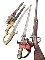 From left to right: two bayonets, a short curved infantry or artillery briquet, a straight infantry officers' sabre, and a carbine.