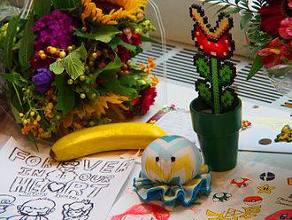 Satoru Iwata - Fans left memorabilia and personalized artwork of various Nintendo video game series, including Mario, Kirby, and The Legend of Zelda, dedicated to Iwata at a memorial in the Nintendo World Store.