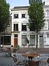 foto van Pand met zadeldak, evenwijdig aan de straat. Lijstgevel met stucdecoraties (XIXc). Gesneden consoles onder de lijst