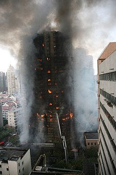 Flames can be seen inside a tall brown-black building frame. Smoke surrounds the gutted structure while a single stream of water from the ground reaches midway up the building.