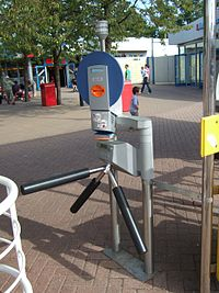 A modern Skidata turnstile at Legoland Windsor. The user inserts a ticket or pass into the orange slot, from which a barcode is read; if access is to be granted, a sensor determines the speed with which the user passes through, and sets the electric motor to turn the turnstile at the corresponding speed.