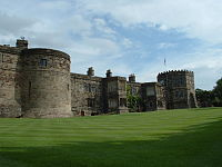 A two-storey castle with a two-storey circular tower on the left and a three-storey octagonal tower on the right. The castle overlooks a green lawn.