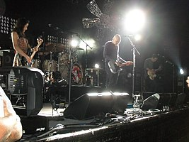 The Smashing Pumpkins perform on a brightly lit stage with a large metal flower hanging over them. From left to right: Nicole Fiorentino—a brunette Caucasian woman wearing a dress—looks at her black bass guitar, Mike Byrne plays a silver drum kit obscured behind his drums, Billy Corgan—a bald, middle-aged Caucasian man wearing a sriped t-shirt and dark pants—plays guitar, and Jeff Schroeder—a Korean male in his 30s with brunette hair—looks at his guitar while playing.